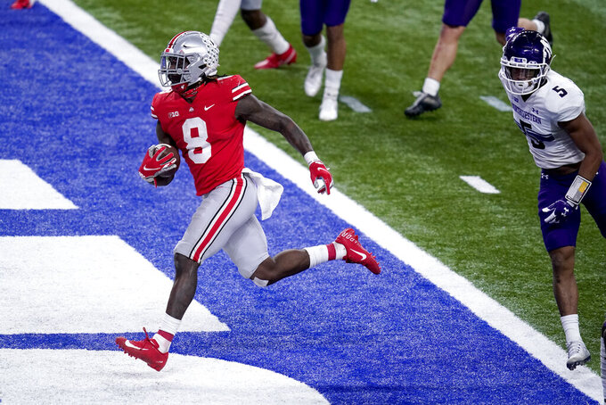 Ohio State running back Trey Sermon (8) scores past Northwestern defensive back JR Pace (5) during the second half of the Big Ten championship NCAA college football game, Saturday, Dec. 19, 2020, in Indianapolis. (AP Photo/Darron Cummings)