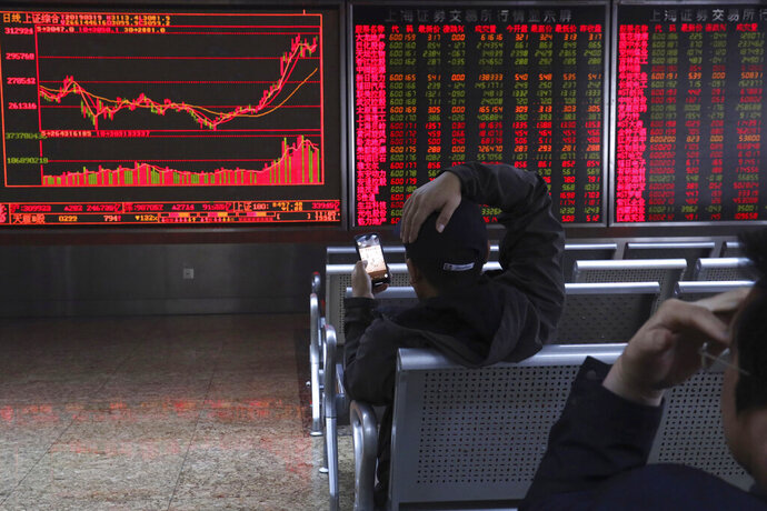 An investor plays a mobile chess game while watching stock prices at a brokerage in Beijing, China, Tuesday, March 19, 2019. Asian shares were mixed in muted trading Tuesday as investors awaited the U.S. Federal Reserve meeting later in the week. (AP Photo/Ng Han Guan)