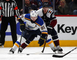 St. Louis Blues right wing Vladimir Tarasenko, front, collects the puck as Colorado Avalanche left wing Gabriel Landeskog defends in the third period of an NHL hockey game Saturday, Feb. 16, 2019, in Denver. The Blues won 3-0. (AP Photo/David Zalubowski)