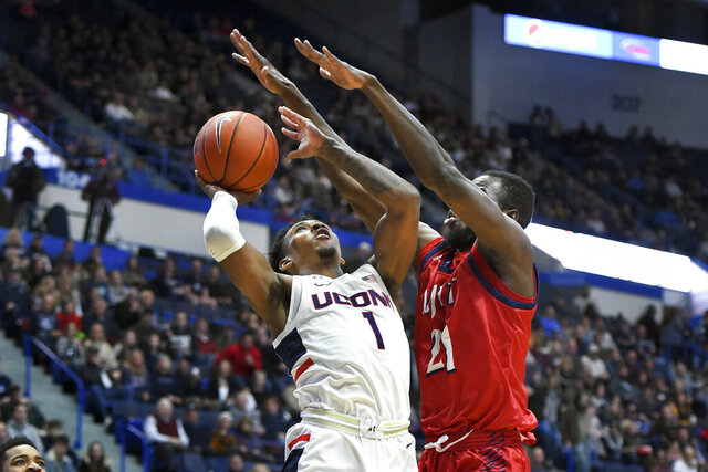 Connecticut's Christian Vital (1) shoots against New Jersey Institute of Technology's Souleymane Diakite (21) in the first half of an NCAA college basketball game Sunday, Dec. 29, 2019, in Hartford, Conn. (AP Photo/Stephen Dunn)