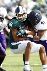Michigan State's Felton Davis (18) is stopped by Northwestern's Jared McGee (41) during the first quarter of an NCAA college football game, Saturday, Oct. 6, 2018, in East Lansing, Mich. (AP Photo/Al Goldis)