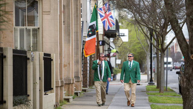 Sinn Fein Society members Bill Bradley, left, and John Lowenthal, right, walk the sidewalk of the St. Patrick's Day parade route in downtown Savannah, Ga., Tuesday, March 17, 2020. Last week, Savannah's mayor announced the city's 196-year-old St. Patrick's Day parade was called off due to coronavirus concerns. (AP Photo/Stephen B. Morton)