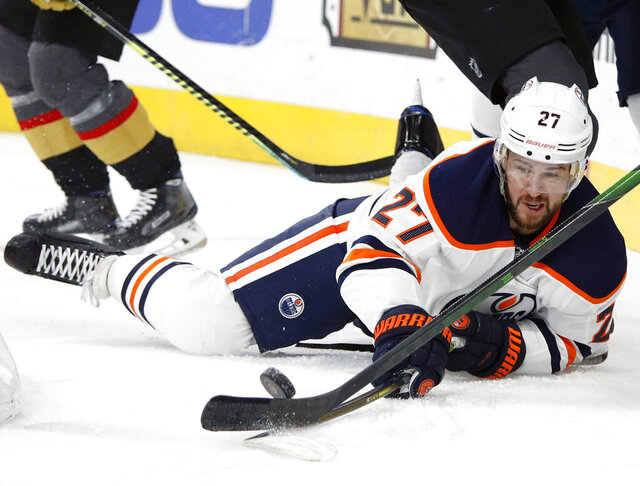 FILE - In this Feb. 26, 2020, file photo, Edmonton Oilers defenseman Mike Green (27) fights for the puck against the Vegas Golden Knights during the first period of an NHL hockey game in Las Vegas. Green and Vancouver's Sven Baertschi are opting out. Dallas defenseman Roman Polak is not reporting for now. And Tampa Bay captain Steven Stamkos is not reporting at full strength. Green and Baertschi joined Calgary defender Travis Hamonic in choosing not to participating in the resumption of the NHL season. Green, like Hamonic, decided not to play for family reasons. (AP Photo/John Locher, File)