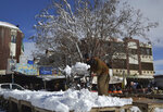 A vendor removes snow from his stall after heavy snowfall in Quetta, capital of Pakistan's southwestern Baluchistan province, Monday, Jan. 13, 2020. Severe winter weather has struck parts of Afghanistan and Pakistan, with heavy snowfall, rains and flash floods that left more than 40 dead, officials said Monday as authorities struggled to clear and reopen highways and evacuate people to safer places. (AP Photo/Arshad Butt)