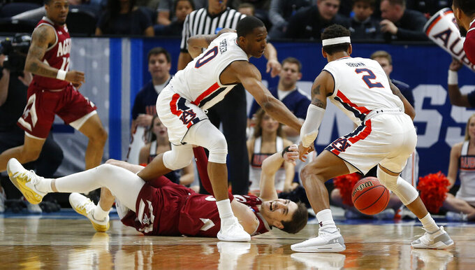 New Mexico State forward Ivan Aurrecoechea, bottom and Auburn's Horace Spencer (0) and Bryce Brown (2) battle for a loose ball in the first half during a first round men's college basketball game in the NCAA Tournament, Thursday, March 21, 2019, in Salt Lake City. (AP Photo/Rick Bowmer)