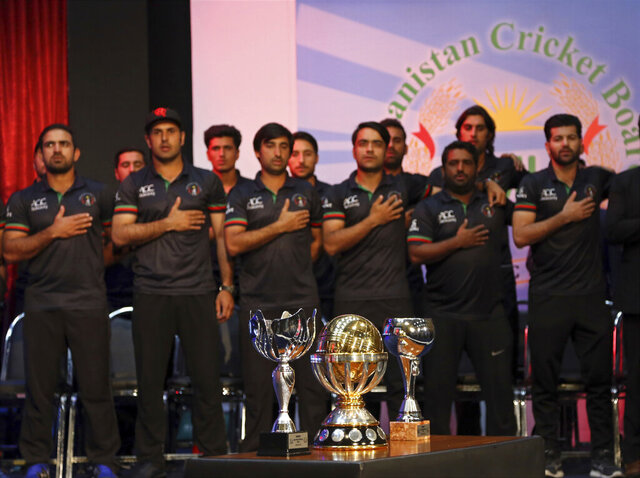 FILE - In this March 27, 2018 file photo, Afghanistan's cricket players stand for the national anthem, during celebrations following their defeat of West Indies in the final of the 2019 World Cup qualification tournament in Kabul, Afghanistan. The national cricket team is beginning a month-long training camp, even as the coronavirus is spreading widely across Afghanistan and an international aid organization warns it was on the brink of a humanitarian crisis. The Afghanistan Cricket Board announced the start of the training camp for its 22 players a day after the government laid out new guidelines to tackle the spread of the virus. Cricket is the most popular sport in Afghanistan. (AP Photo/Rahmat Gul)