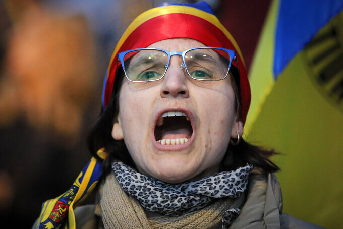 A woman shouts slogans outside the Cotroceni Presidential Palace in Bucharest, Romania, Saturday, April 10, 2021. Marchers took to the streets Saturday in the Romanian capital of Bucharest to protest restrictive measures to fight the spread of COVID-19 even as new daily infections and deaths rose in the European Union nation. (AP Photo/Vadim Ghirda)