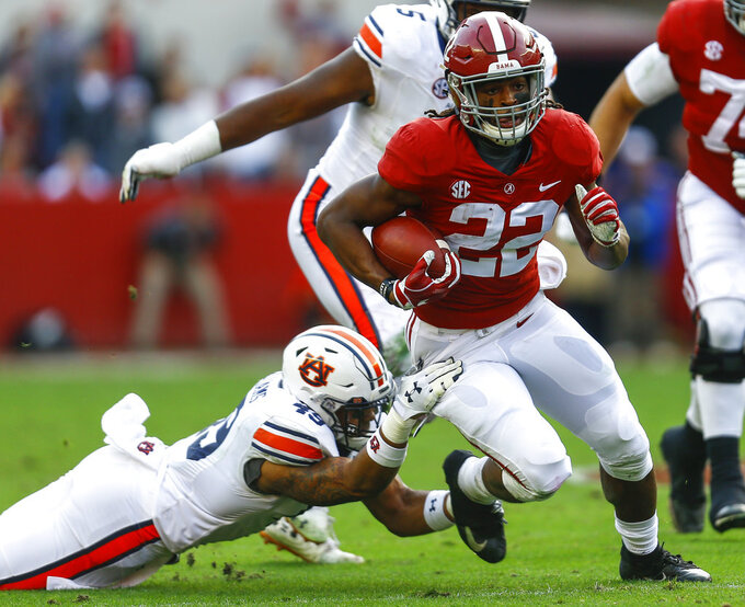 Alabama running back Najee Harris (22) carries the ball as Auburn linebacker Darrell Williams (49) tries to tackle him during the first half of an NCAA college football game, Saturday, Nov. 24, 2018, in Tuscaloosa, Ala. (AP Photo/Butch Dill)