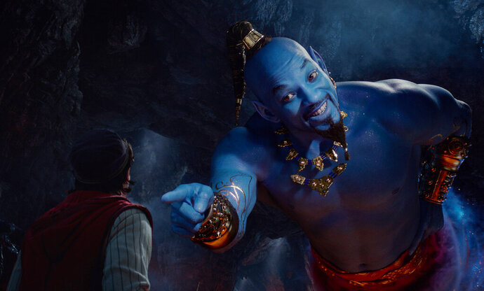 This image released by Disney shows Mena Massoud as Aladdin, left, and Will Smith as Genie in Disney's live-action adaptation of the 1992 animated classic