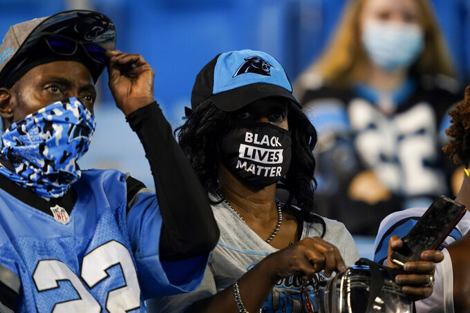 Fans wearing face coverings watch during warm ups an NFL football game between the Carolina Panthers and the Atlanta Falcons Thursday, Oct. 29, 2020, in Charlotte, N.C. (AP Photo/Gerry Broome)
