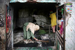 A Muslim woman cleans a shrine burnt in Tuesday's violence in New Delhi, India, Thursday, Feb. 27, 2020. India accused a U.S. government commission of politicizing communal violence in New Delhi that killed at least 30 people and injured more than 200 as President Donald Trump was visiting the country. The violent clashes between Hindu and Muslim mobs were the capital's worst communal riots in decades and saw shops, Muslim shrines and public vehicles go up in flames. (AP Photo/Altaf Qadri)