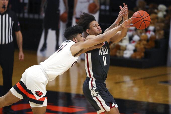 Oregon State's Isaiah Johnson (24) blocks a pass to Washington State's DJ Rodman (11) during the first half of an NCAA college basketball game in Corvallis, Ore., Saturday, Feb. 6, 2021. (AP Photo/Amanda Loman)