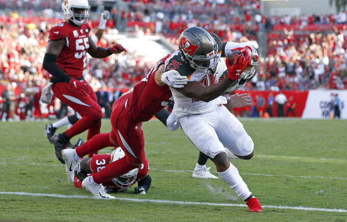 Tampa Bay Buccaneers running back Peyton Barber (25) slips a tackle by Arizona Cardinals linebacker Joe Walker (59) to score on a 1-yard touchdown run during the second half of an NFL football game Sunday, Nov. 10, 2019, in Tampa, Fla. (AP Photo/Mark LoMoglio)