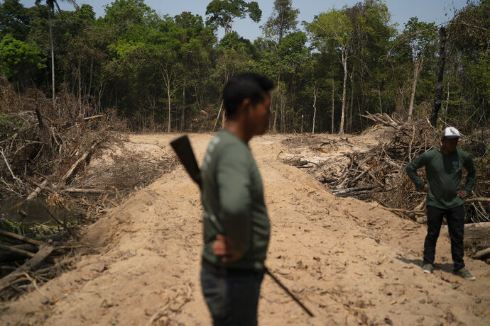FILE - In this Aug. 31, 2019 file photo, Monhire Menkragnotire, of the Kayapo indigenous community, center, surveys an area where illegal loggers opened a 8km road to enter Menkragnotire indigenous lands, where logging is illegal, on the border with the Biological Reserve Serra do Cachimbo, top, where logging is also illegal, in Altamira, Para state, Brazil. Documents seen by The Associated Press show that Brazil's government has begun legal procedures to shut down three of the state's four environmental protection offices that belong to the government's Brazilian Institute of the Environment and Renewable Natural Resources, or Ibama, in charge of defending the country's forests from illegal deforestation, land grabbing, or fires. (AP Photo/Leo Correa, File)