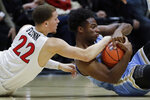 San Diego State guard Malachi Flynn (22) battles San Diego Christian guard Jamario Harris for a loose ball during the first half of an NCAA college basketball game Wednesday, Dec. 18, 2019, in San Diego. (AP Photo/Gregory Bull)