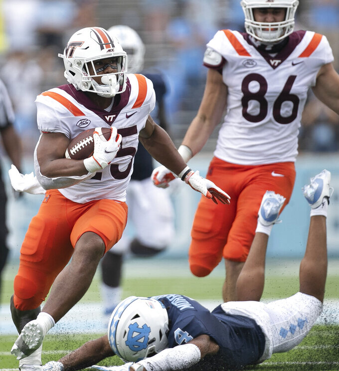 Virginia Tech's Khalil Herbert (25) breaks away from North Carolina's Trey Morrison (4) for a five-yard gain in the third quarter of an NCAA college football game, Saturday, Oct. 10, 2020 at Kenan Stadium in Chapel Hill, N.C. (Robert Willett/The News & Observer via AP)