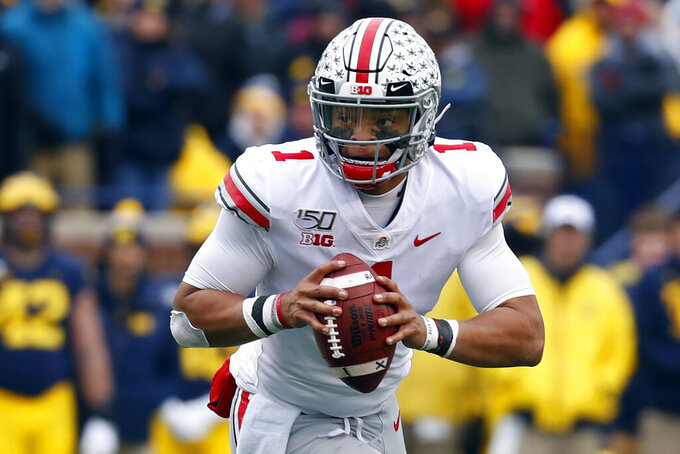 FILE - In this Nov. 30, 2019, file photo, Ohio State quarterback Justin Fields rolls out to throw against Michigan during the first half of an NCAA college football game in Ann Arbor, Mich. Ohio State opens preseason training camp on Thursday, Aug. 6, 2020, with strict coronavirus protocols in place and under a cloud of uncertainty about whether a revised 10-game season will even be played at all. (AP Photo/Paul Sancya, File)