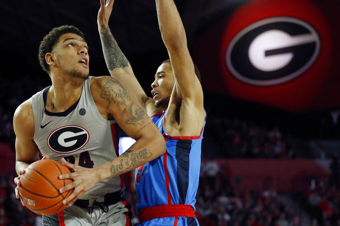 Georgia's Rodney Howard (24) looks to shoot while defended by Mississippi forward KJ Buffen (5) during an NCAA college basketball game in Athens, Ga., Saturday, Jan. 25, 2020. (Joshua L. Jones/Athens Banner-Herald via AP)
