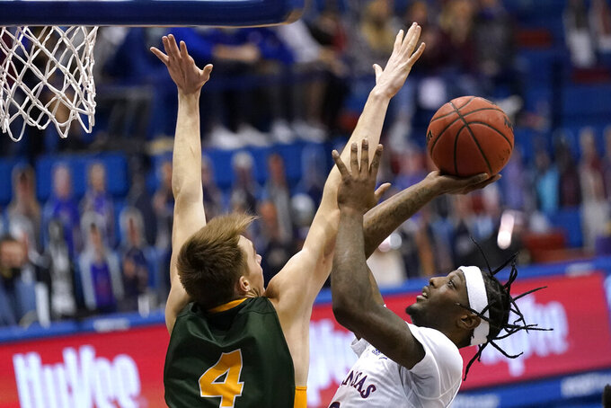 Kansas' Marcus Garrett, right, shoots under pressure from North Dakota State's Grant Nelson (4) during the second half of an NCAA college basketball game Saturday, Dec. 5, 2020, in Lawrence, Kan. (AP Photo/Charlie Riedel)