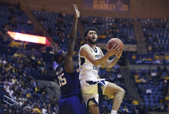 West Virginia guard Jermaine Haley (10) drive while defended by TCU forward JD Miller (15) during the first overtime of an NCAA college basketball game Tuesday, Feb. 26, 2019, in Morgantown, W.Va. (AP Photo/Raymond Thompson)
