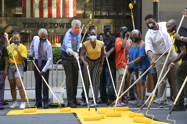 Mayor Bill de Blasio, third from left, participates in painting Black Lives Matter on Fifth Avenue in front of Trump Tower, Thursday, July 9, 2020, in New York. The mayor's wife, Chirlane McCray, is fourth from left and Rev. Al Sharpton is second from left. (AP Photo/Mark Lennihan)