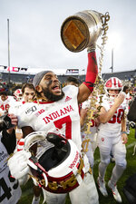 Indiana linebacker Reakwon Jones (7) celebrates with the Old Oaken Bucket following an NCAA college football game against Purdue in West Lafayette, Ind., Saturday, Nov. 30, 2019. Indiana defeated Purdue 44-41 in double overtime. (AP Photo/Michael Conroy)