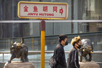 People wearing face masks walk past statues of bulls in Beijing, Friday, Feb. 28, 2020. Asian stock markets fell further Friday on spreading virus fears, deepening an global rout after Wall Street endured its biggest one-day drop in nine years. (AP Photo/Mark Schiefelbein)