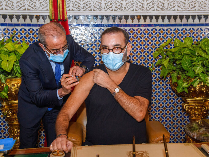 In this photo released by the Royal Palace, Morocco's King Mohammed VI, right, receives the COVID-19 vaccine at the Royal Palace in Fes, as he launches his country's coronavirus vaccination campaign, Thursday Jan. 28, 2021. The North African kingdom received its first shipments of vaccine doses in recent days from China's Sinopharm and Anglo-Swedish drug maker AstraZeneca. (Moroccan Royal Palace via AP)