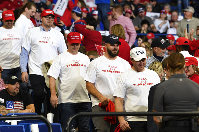 In this Nov. 4, 2019, photo, people wearing shirts with the words
