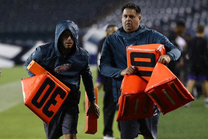 Workers remove sideline markers after a storm ended a preseason NFL football game between the Philadelphia Eagles and the Baltimore Ravens, Thursday, Aug. 22, 2019, in Philadelphia. (AP Photo/Michael Perez)