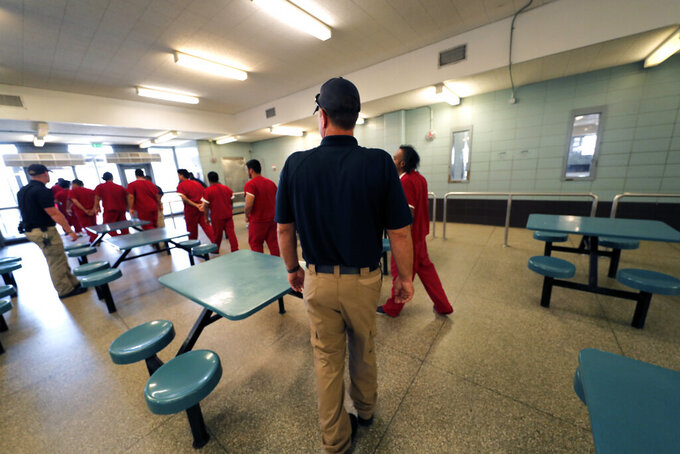 FILE — Immigration detainees leave the cafeteria under the watch of guards during a media tour at the Winn Correctional Center in Winnfield, La., in this Thursday, Sept. 26, 2019 file photo. The number of detainees nationwide has more than doubled since the end of February 2021, to nearly 27,000, according to recent data from U.S. Immigration and Customs Enforcement. (AP Photo/Gerald Herbert, File)