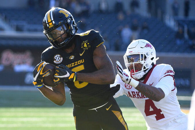 Missouri wide receiver Keke Chism, left, catches a pass as Arkansas defensive back Malik Chavis defends during the second half of an NCAA college football game Saturday, Dec. 5, 2020, in Columbia, Mo. (AP Photo/L.G. Patterson)