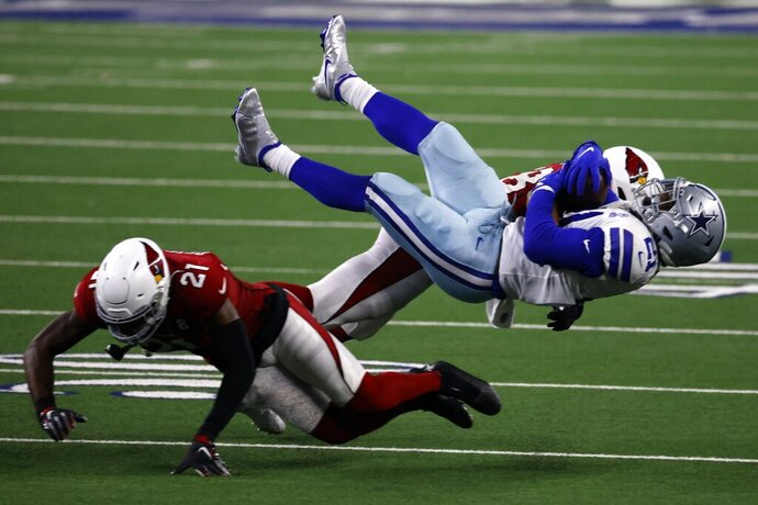 Arizona Cardinals cornerback Patrick Peterson (21) and linebacker Jordan Hicks, rear, combine to tackle Dallas Cowboys running back Ezekiel Elliott, right front, after a short gain in the second half of an NFL football game in Arlington, Texas, Monday, Oct. 19, 2020. (AP Photo/Ron Jenkins)