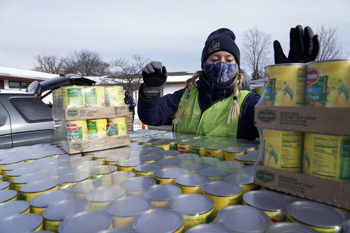 Hunger Task Force Workers distribute food, Thursday, Jan. 28, 2021, at McGovern Park in Milwaukee. The Republican-controlled Wisconsin Assembly was poised Thursday to repeal Democratic Gov. Tony Evers' mask mandate, a move that would jeopardize more than $49 million in federal food assistance. (AP Photo/Morry Gash)