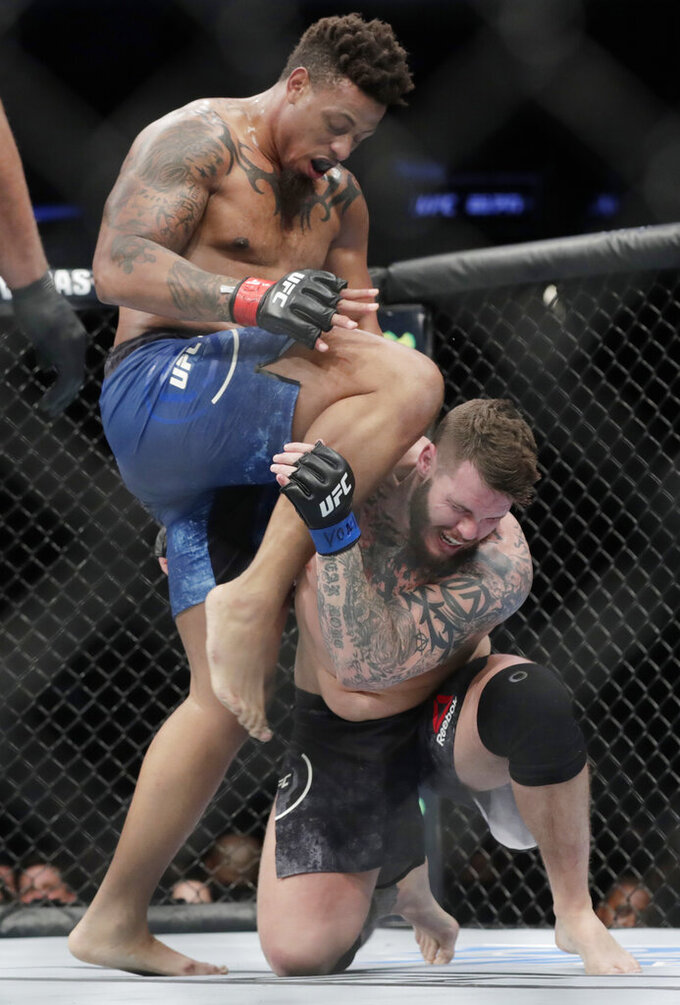 Greg Hardy knees Allen Crowder on the head during the second round of a heavyweight mixed martial arts bout at UFC Fight Night, early Sunday, Jan. 20, 2019, in New York. Crowder won the fight after Hardy was disqualified for an illegal knee in the second round. (AP Photo/Frank Franklin II)