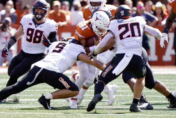 Oklahoma State defensive end Brock Martin (9) and linebacker Malcolm Rodriguez (20) stop Texas quarterback Casey Thompson (11) on fourth down during the second half of an NCAA college football game in Austin, Texas, Saturday, Oct. 16, 2021. (AP Photo/Chuck Burton)