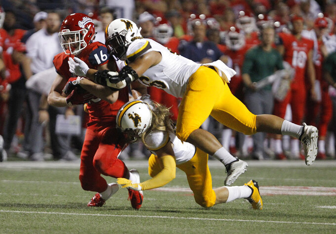 Fresno State tight end Jared Rice (16) is brought down by Wyoming defenders during the first half of an NCAA college football game in Fresno, Calif., Saturday, Oct. 13, 2018. (AP Photo/Gary Kazanjian)