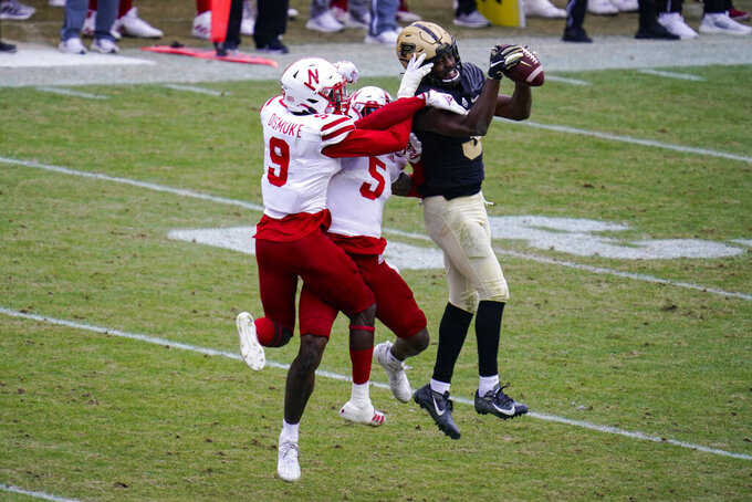 Purdue wide receiver David Bell (3) makes a catch over Nebraska safety Marquel Dismuke (9) and cornerback Cam Taylor-Britt (5) on his way to an 89-yard touchdown during the fourth quarter of an NCAA college football game in West Lafayette, Ind., Saturday, Dec. 5, 2020. (AP Photo/Michael Conroy)