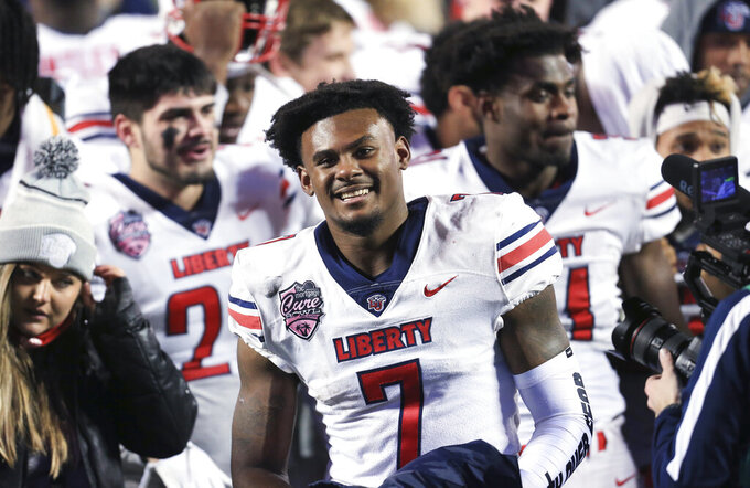 Liberty quarterback Malik Willis (7) celebrates with teammates after the team's overtime win over Coastal Carolina in the Cure Bowl NCAA college football game Saturday, Dec. 26, 2020, in Orlando, Fla. (AP Photo/Matt Stamey)