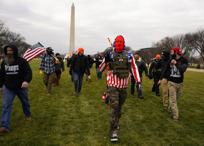 FILE - In this Jan. 6, 2021, file photo, people march with those who say they are members of the Proud Boys as they attend a rally in Washington in support of President Donald Trump. In its annual report set to be released Monday, Feb. 1, 2021, the Southern Poverty Law Center said it identified 838 active hate groups operating across the U.S. in 2020. The SPLC's report comes out nearly a month after a mostly white mob of Trump supporters and members of far-right groups violently breached the U.S. Capitol building. (AP Photo/Carolyn Kaster, File)