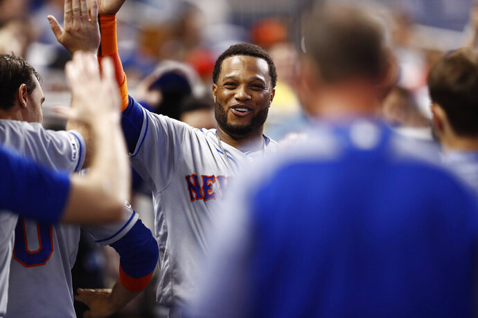 New York Mets' Robinson Cano (24) celebrates in the dugout after scoring during the fourth inning of a baseball game against the Miami Marlins on Sunday, July 14, 2019, in Miami. (AP Photo/Brynn Anderson)