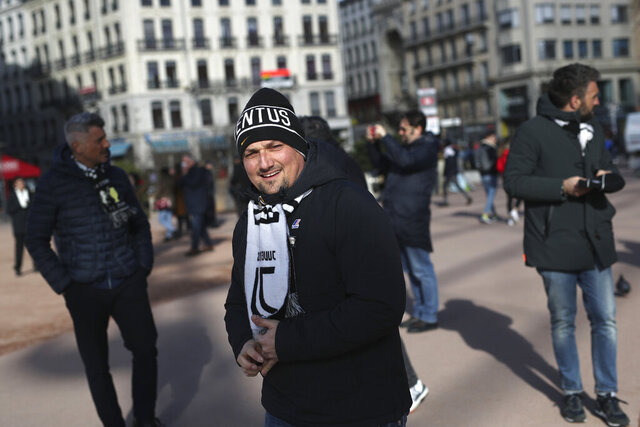 A Juventus supporter visits Lyon, central France, ahead of the Champions League , round of 16th, first leg match Lyon against Juventus, Wednesday Feb. 26, 2020. Up to 3,000 Juventus fans are expected. As the coronavirus cases clustered in northern Italy kept climbing and European countries reported new ones with Italian travel ties Tuesday, authorities across the continent tried to strike a balance between taking prudent public health measures and preventing panic. (AP Photo/Daniel Cole)