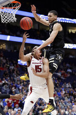 Vanderbilt forward Dylan Disu (1) fouls Arkansas guard Mason Jones (15) in the second half of an NCAA college basketball game in the Southeastern Conference Tournament Wednesday, March 11, 2020, in Nashville, Tenn. Arkansas won 86-73. (AP Photo/Mark Humphrey)