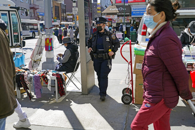 New York Police Department Officer Joanna Derkacz keeps an eye on pedestrians passing her on a busy stretch of Main Street in Flushing, Tuesday, March 30, 2021, in the Queens borough of New York. Police have stepped up patrols in the largely Asian neighborhood in the wake of Monday's vicious attack on a 65 year-old Asian woman in midtown Manhattan during which no bystanders intervened to help. (AP Photo/Kathy Willens)