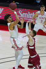 Utah forward Timmy Allen, left, shoots over Stanford guard Noah Taitz during the second half of an NCAA college basketball game Thursday, Jan. 14, 2021, in Salt Lake City. (AP Photo/Rick Bowmer)