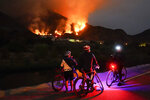 Cyclists rest along a trail as the Ranch Fire burns, Thursday, Aug. 13, 2020, in Azusa, Calif. Heat wave conditions were making difficult work for fire crews battling brush fires and wildfires across Southern California. (AP Photo/Marcio Jose Sanchez)