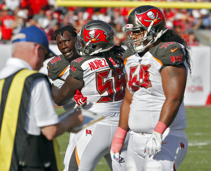 Tampa Bay Buccaneers defensive end Jason Pierre-Paul, let, has to be restrained by defensive tackle Rakeem Nunez-Roches (56) from getting to defensive tackle Vita Vea (50) after an Arizona Cardinals run during the second half of an NFL football game Sunday, Nov. 10, 2019, in Tampa, Fla. (AP Photo/Mark LoMoglio)