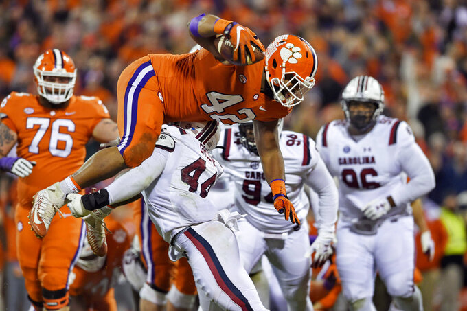 Clemson's Christian Wilkins dives over South Carolina's Sherrod Greene to score a touchdown during the first half of an NCAA college football game Saturday, Nov. 24, 2018, in Clemson, S.C. (AP Photo/Richard Shiro)