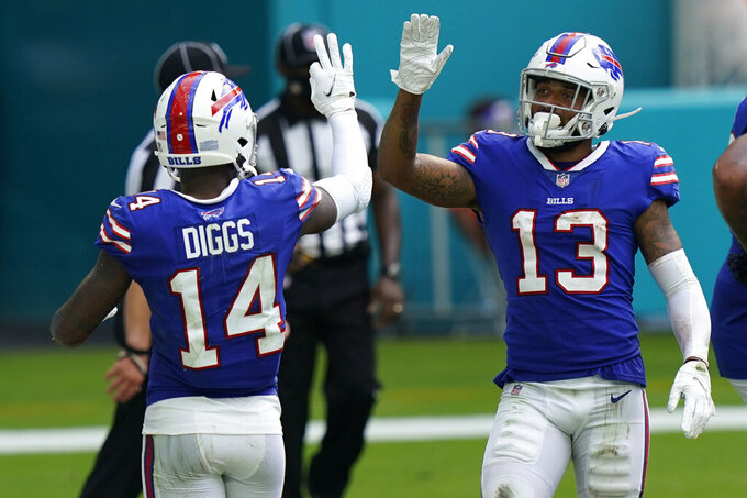 Buffalo Bills wide receiver Stefon Diggs (14) congratulates wide receiver Gabriel Davis (13) after Davis scored a touchdown, during the second half of an NFL football game against the Miami Dolphins, Sunday, Sept. 20, 2020, in Miami Gardens, Fla. The Bills defeated the Dolphins 31-28. (AP Photo/Lynne Sladky)