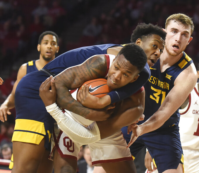West Virginia forward Gabe Osabuohien, top, tries to get the ball from Oklahoma forward Kristian Doolittle (21) during the first half of an NCAA college basketball game in Norman, Okla., Saturday, Feb. 8, 2020. (AP Photo/Kyle Phillips)